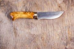 Cuchillo hecho a mano del acero y del latón, con una manija hecha del membrillo de madera Cuchillo en el viejo fondo de madera Fotografía de archivo