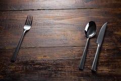 Cuchillo inoxidable de la cuchara de la bifurcación en la sobremesa de madera Fotografía de archivo libre de regalías