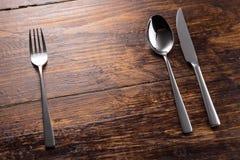 Cuchillo inoxidable de la cuchara de la bifurcación en la sobremesa de madera Fotos de archivo libres de regalías