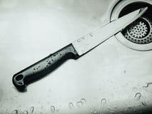 Cuchillo inoxidable después de limpio y del descenso del agua en fregadero con el murde Foto de archivo libre de regalías