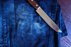Cuchillo para cortar el delantal del pan y del dril de algodón imagen de archivo