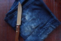 Cuchillo para cortar el delantal del pan y del dril de algodón fotos de archivo