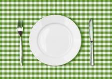 Cuchillo, placa blanca y bifurcación en el paño de mesa de picnic verde Fotos de archivo