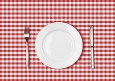 Cuchillo, placa blanca y bifurcación en el paño de mesa de picnic rojo Imagenes de archivo