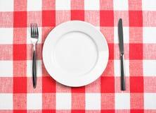 Cuchillo, placa blanca y fork en mantel controlado fotos de archivo libres de regalías