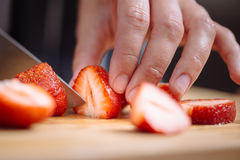 Cuchillo que corta una fresa Fotografía de archivo libre de regalías