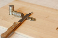 Cuchillo que corta una pila de moneda Concepto de recortes presupuestarios, ahorros, r fotos de archivo