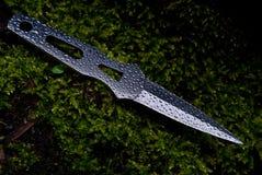 Cuchillo que lanza en las gotas del agua Foto de archivo