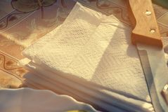 Cuchillo, servilletas de papel y una placa blanca en una tabla Fotografía de archivo
