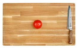 Cuchillo sostenido y tomate Foto de archivo libre de regalías