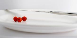 Cuchillo y bayas en una placa blanca Foto de archivo libre de regalías