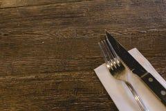 Cuchillo y bifurcación en una tabla de madera con la servilleta blanca imagen de archivo libre de regalías
