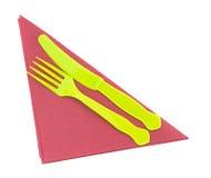 Cuchillo y bifurcación plásticos brillantes en la servilleta roja, servilleta Imagenes de archivo