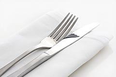 Cuchillo y fork en el lino blanco Fotos de archivo