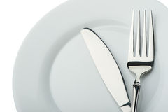 Cuchillo y fork en una placa Foto de archivo libre de regalías