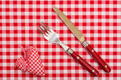 Cuchillo y fuerte con el corazón y el arco a cuadros rojos Fotos de archivo