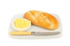 Cuchillo y mantequilla del rollo de pan Fotografía de archivo