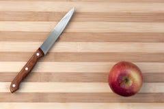 Cuchillo y manzana de cocina en el tablero de madera Fotografía de archivo libre de regalías