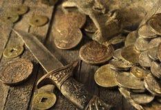Cuchillo y monedas viejas, con efecto de la textura del grunge Imágenes de archivo libres de regalías