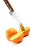 Cuchillo y naranja cortados a medias Imágenes de archivo libres de regalías