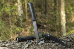 Cuchillo y pedernal en el tocón en el bosque que acampa en naturaleza Supervivencia en el salvaje fotos de archivo