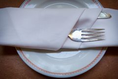 Cuchillo y servilleta de la bifurcación en el plato Fotos de archivo