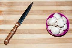 Cuchillo y setas en cuenco Imagen de archivo