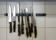 Cuchillos de cocina grandes y aceros del afilamiento que cuelgan en un tenedor magnético en la pared tejada, espacio de la copia imagen de archivo libre de regalías
