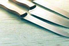 Cuchillos de cocina sentados en un fondo de madera Foto de archivo libre de regalías