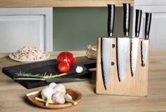 Cuchillos en el estante magnético que coloca una tabla Foto de archivo libre de regalías