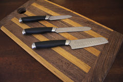 Cuchillos en una tabla de cortar Fotografía de archivo libre de regalías