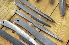 Cuchillos que lanzan en fondo de madera Foto de archivo