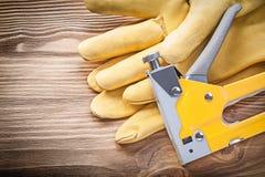 Cucia con punti metallici i guanti della sicurezza della pistola sul concetto della costruzione del bordo di legno Fotografia Stock