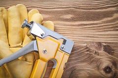 Cucia con punti metallici i guanti protettivi della pistola sul concep della costruzione del bordo di legno Fotografia Stock
