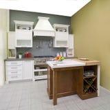 Cucina bianca contemporanea con un'isola di legno marrone Immagine Stock