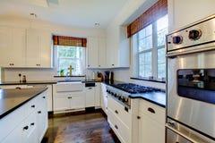 Cucina bianca di lusso con i pavimenti scuri. fotografia stock libera da diritti