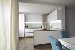 Cucina bianca moderna e luminosa con una progettazione semplice Immagini Stock Libere da Diritti