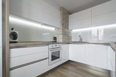 Cucina bianca moderna e luminosa con una progettazione semplice Fotografia Stock Libera da Diritti
