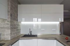 Cucina bianca moderna e luminosa con una progettazione semplice Immagini Stock