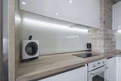 Cucina bianca moderna e luminosa con una progettazione semplice Immagine Stock Libera da Diritti