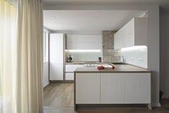 Cucina bianca moderna e luminosa con una progettazione semplice Fotografia Stock