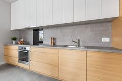 Cucina con il piano di lavoro concreto e la mobilia di legno fotografia stock