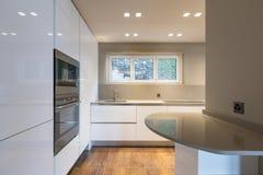 Cucina con mobilia bianca moderna e l'ultimo applia della generazione immagine stock libera da diritti