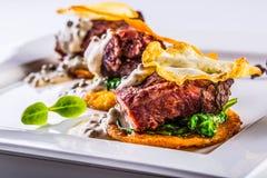 Cucina culinaria Ricetta: Le guance della carne di maiale del Confit con spinaci verdi lascia la salsa di funghi del sedano ed il Fotografie Stock