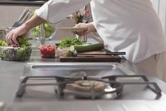 Cucina dell'annuncio pubblicitario di Preparing Salad In del cuoco unico Fotografia Stock