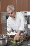 Cucina dell'annuncio pubblicitario di Preparing Salad In del cuoco unico Immagini Stock