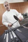 Cucina dell'annuncio pubblicitario di Sharpening Knives In del cuoco unico Immagine Stock