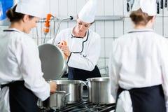 Cucina della mensa con i cuochi unici durante il servizio Fotografie Stock Libere da Diritti