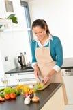 Cucina delle verdure di taglio della donna che sta felice Immagini Stock Libere da Diritti