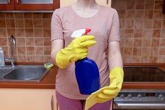Cucina di pulizia con uno spruzzo grasso del dispositivo di rimozione e spugna, giovane donna in guanti di gomma gialli che tengo immagine stock